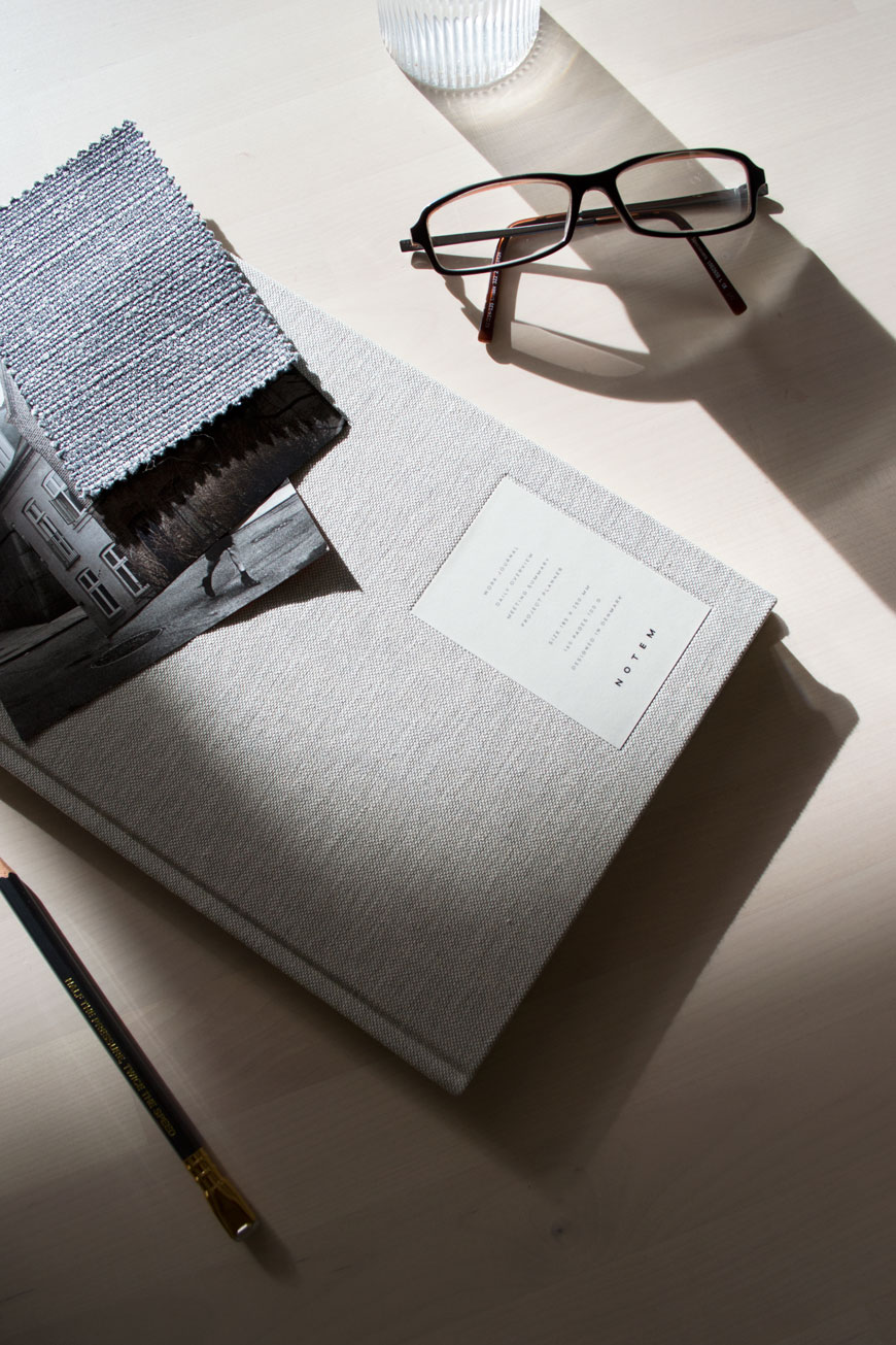 A grey cloth covered diary from NABO sitting on a desk next to a pair of glasses.