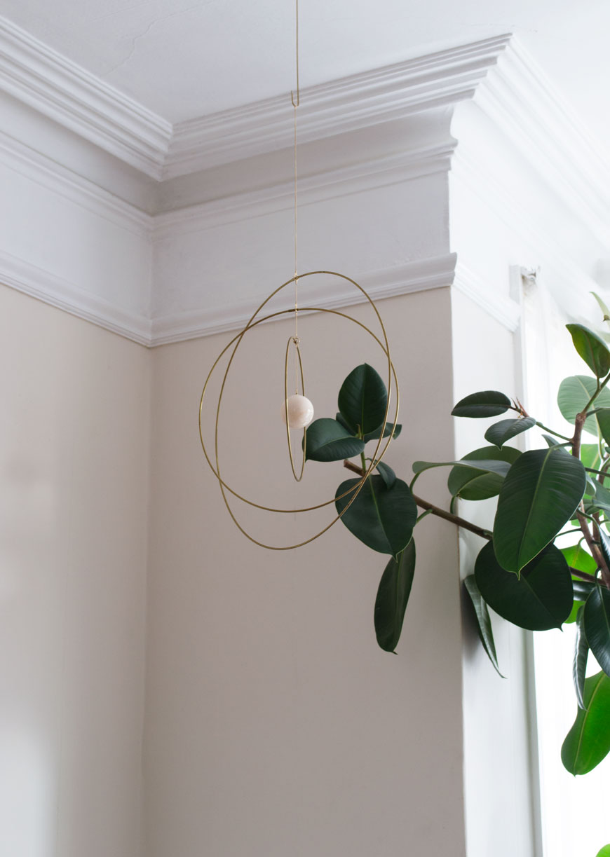 how to style your home for winter with a brass and marble mobile from NABO which hangs from the ceiling next to a tall rubber tree.