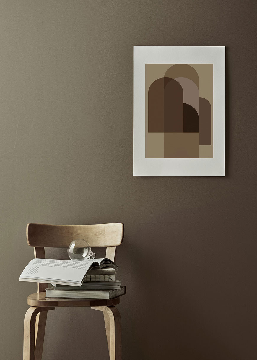 A graphic print in warm amber and rustic tones mounted on a grey green wall.