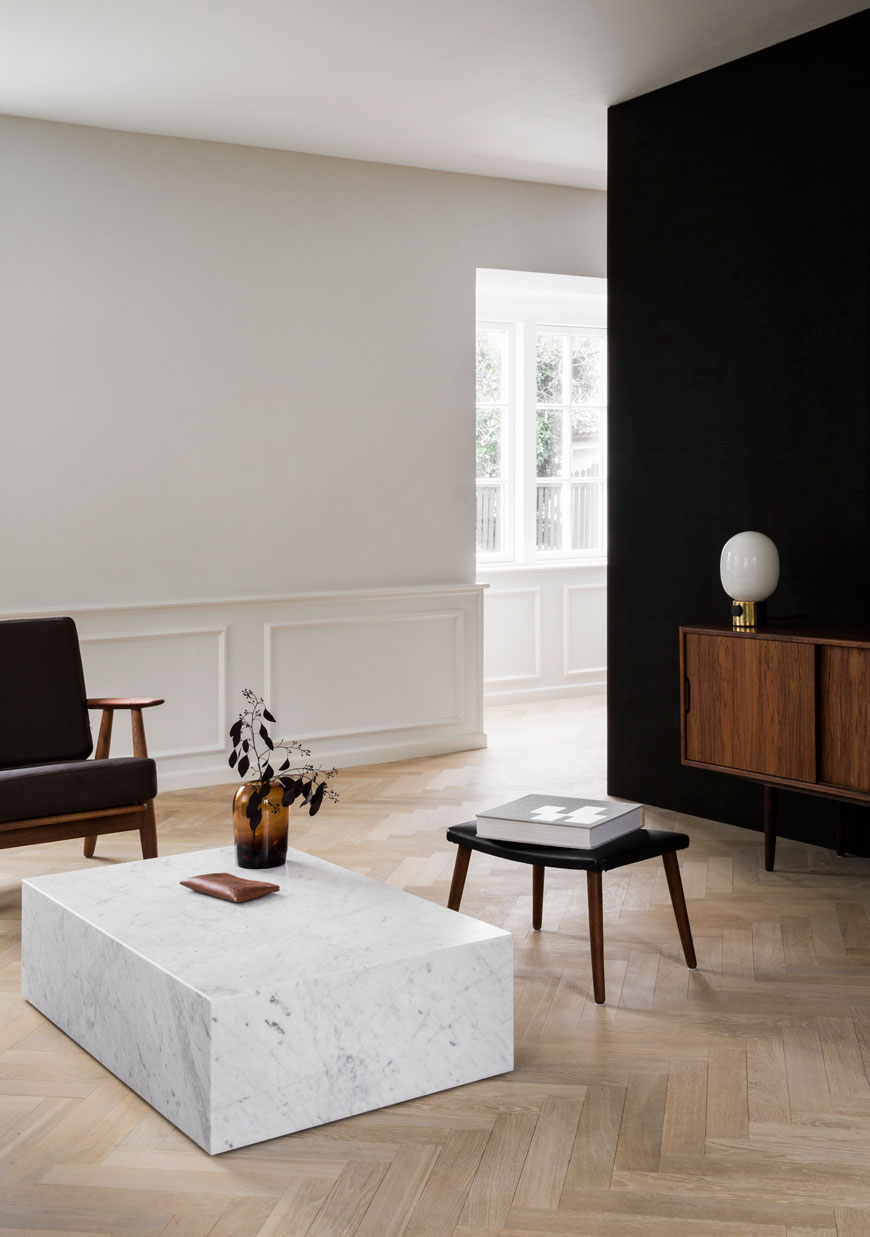 A minimalist Scandinavian living room with a marble coffee table and warm amber glass vase on top