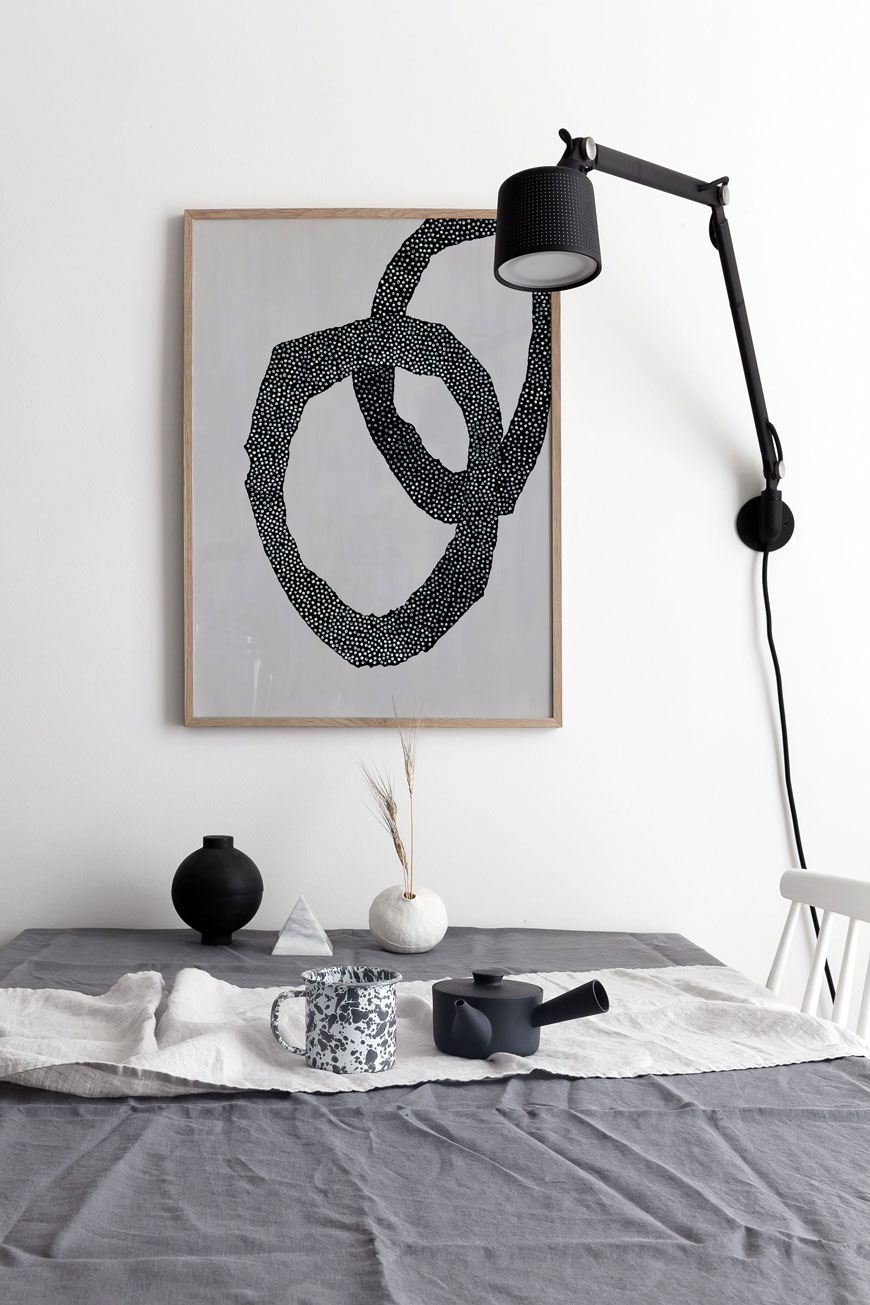 Framed monochrome abstract wall art hanging above the dining table with a black Vipp wall lamp.