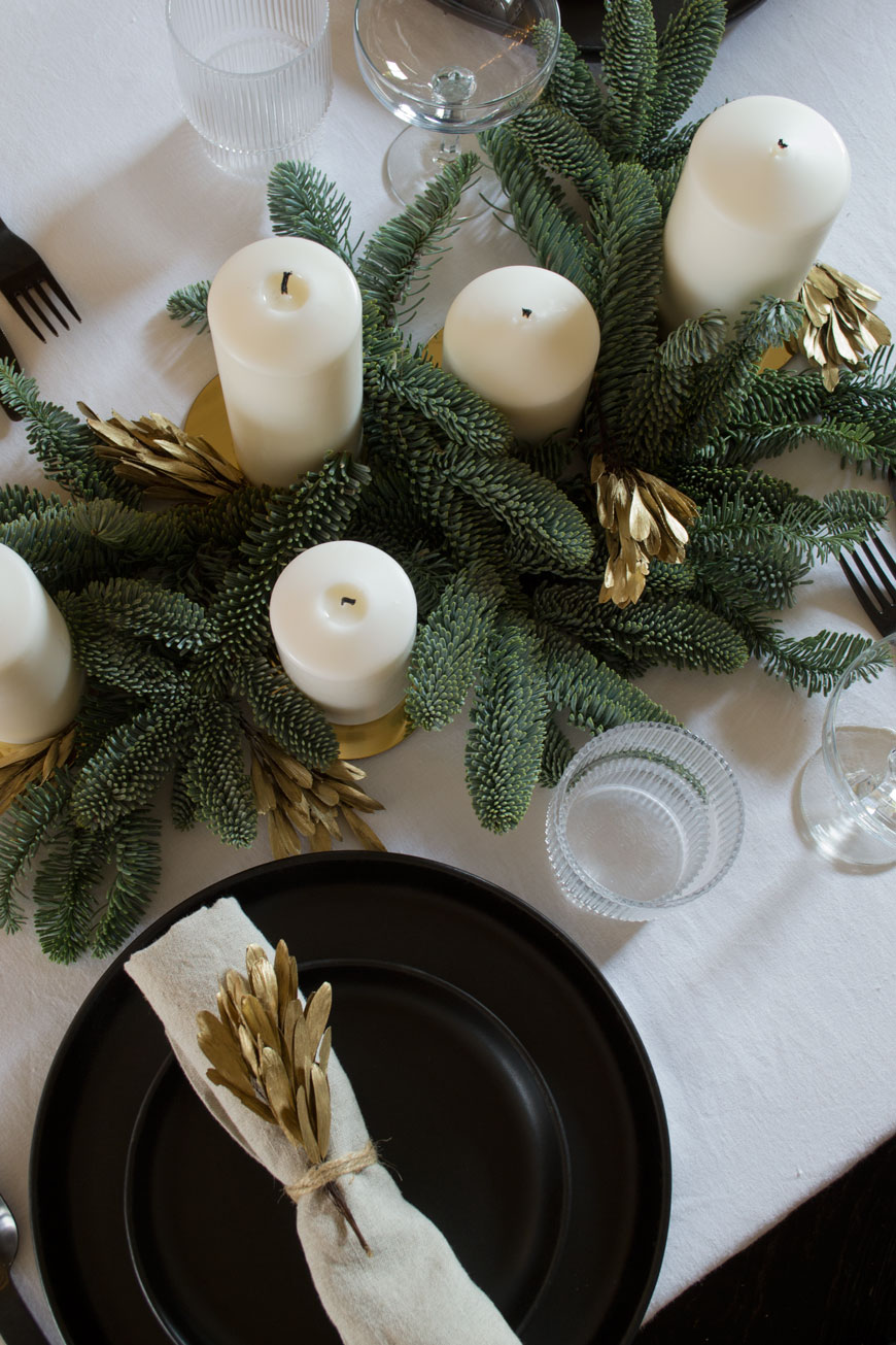 A minimally styled blue spruce and white candle table centrepiece for a very Nordic Christmas.