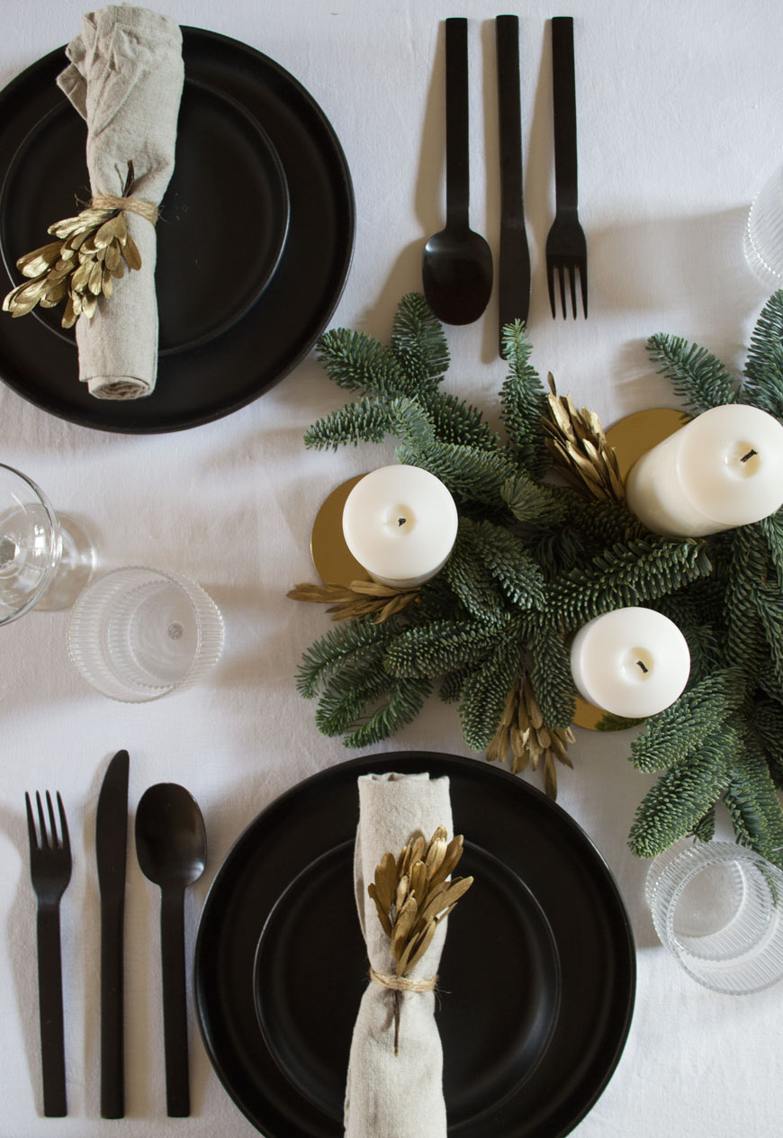 Black, white and gold Nordic Christmas table styling with black plates and cutlery.