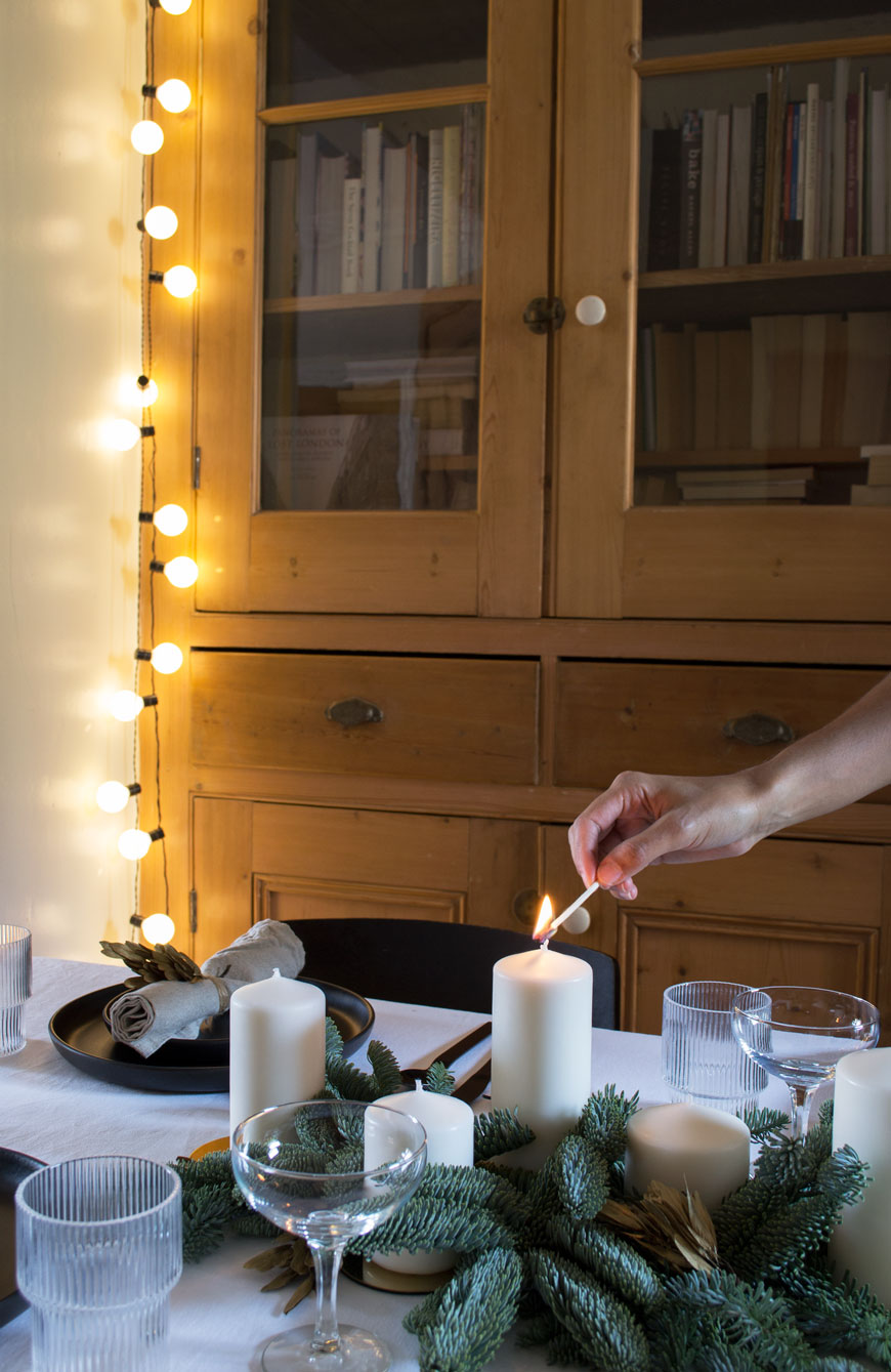 Lighting candles on the table I styled in our dining room to share our Nordic Christmas decorations and styling