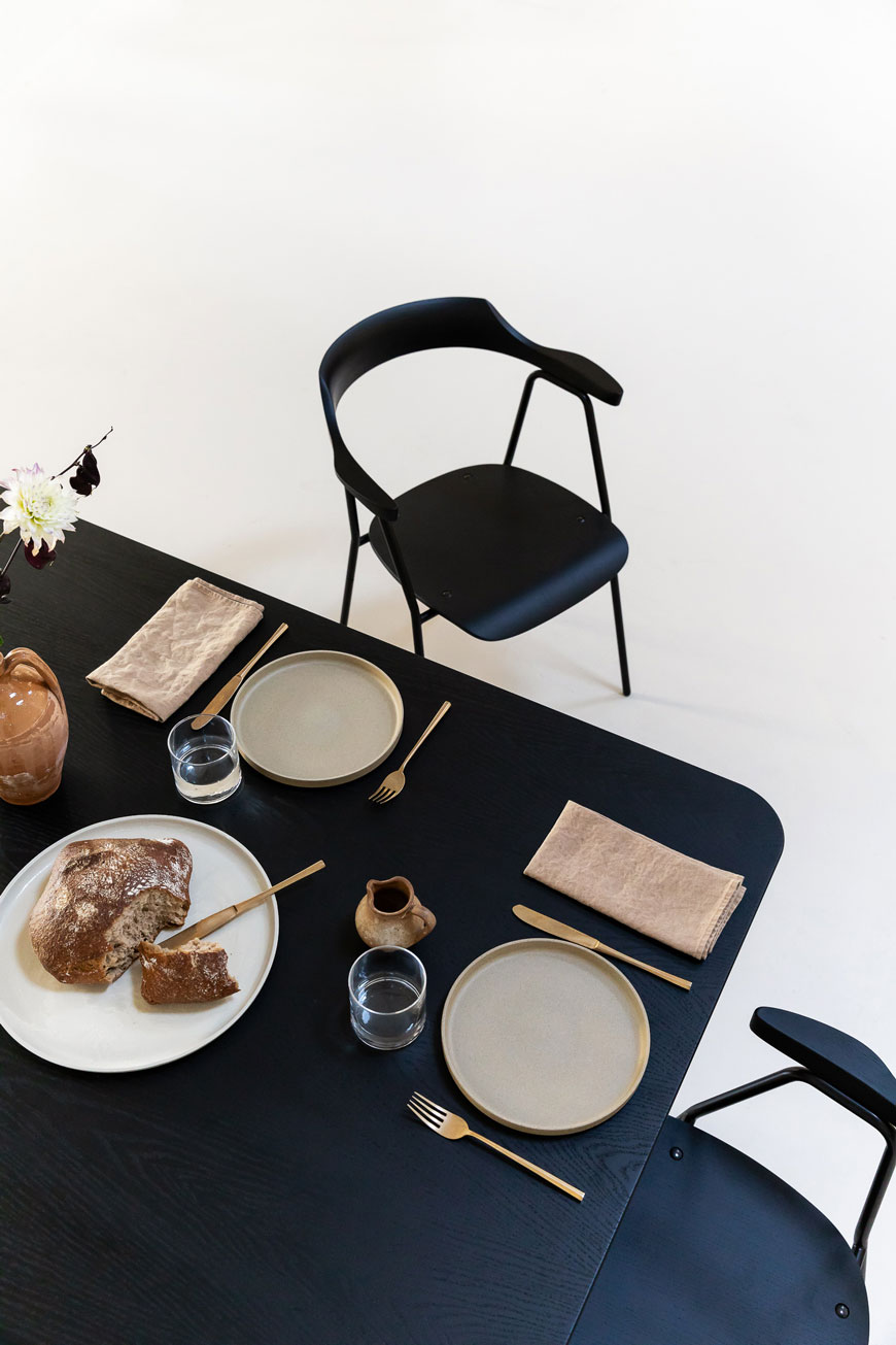 Minimalist black dining chair designed by Rex Kralj and a simple, minimalist table setting.