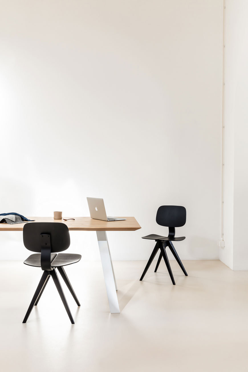 The black Mosquito chair sits in a minimalist office space, designed by Rex Kralj.