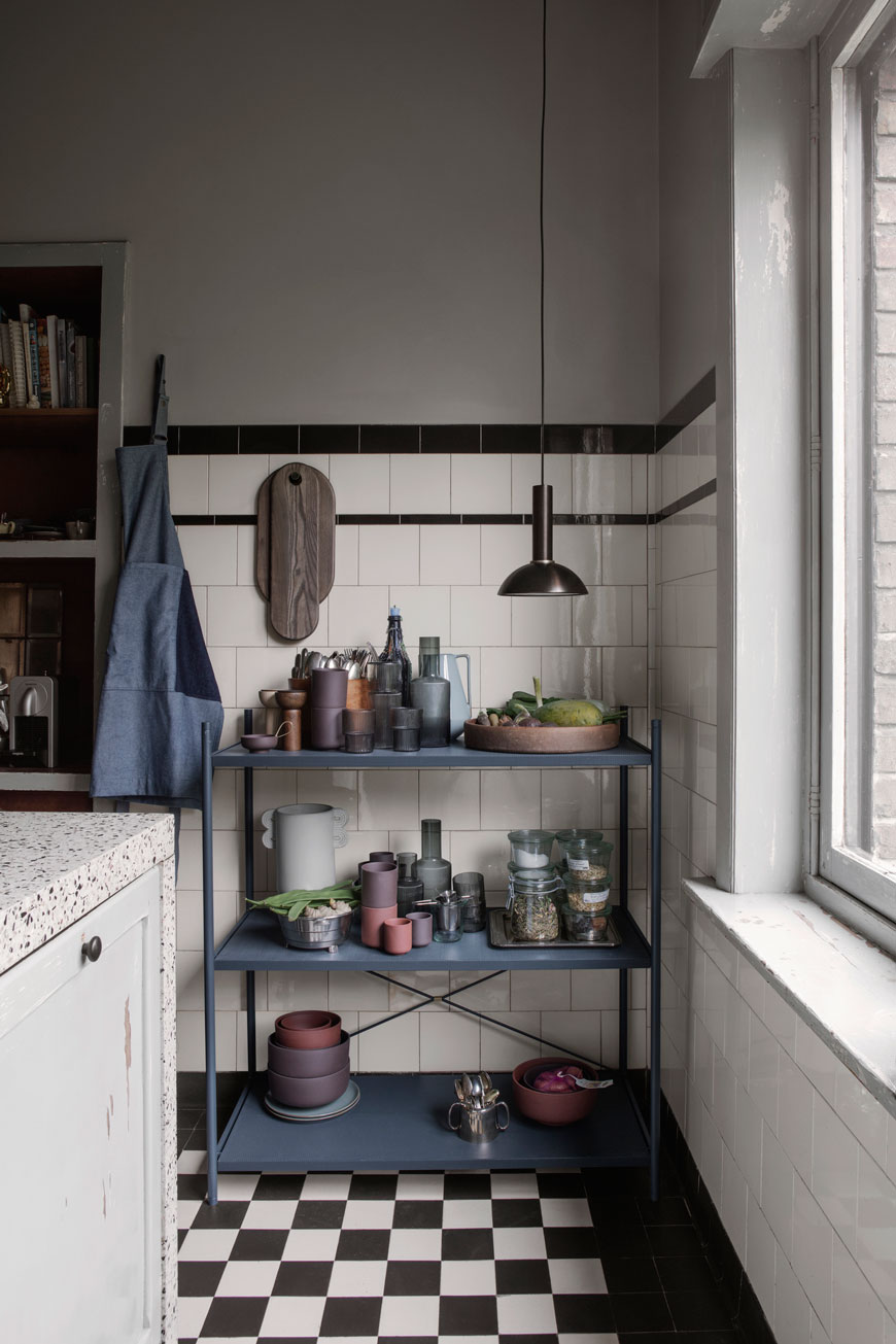 Deep blue open shelves in a moody kitchen, designed by Ferm Living.