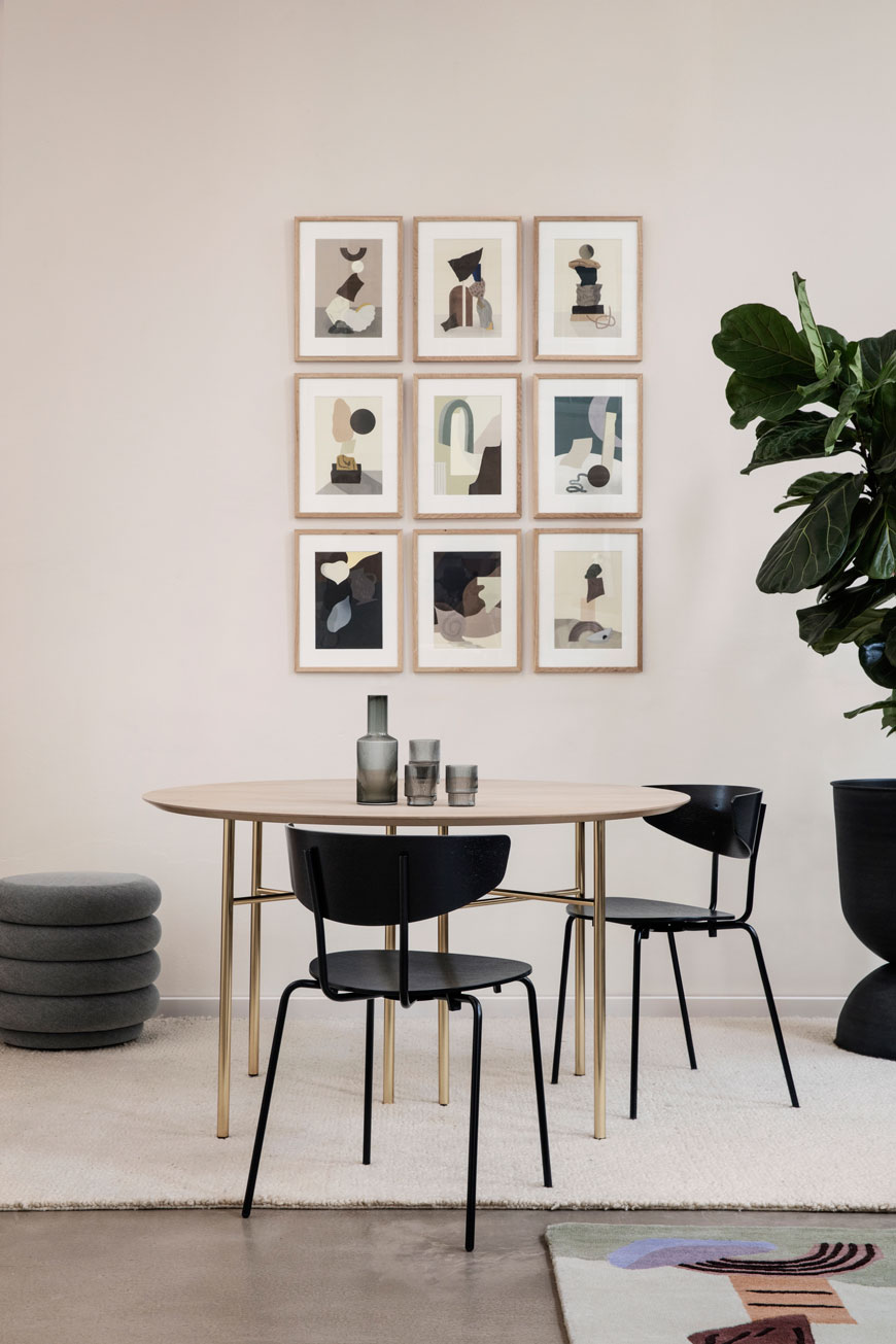 A gallery wall of abstract art in a dining room setting, designed by Ferm Living.