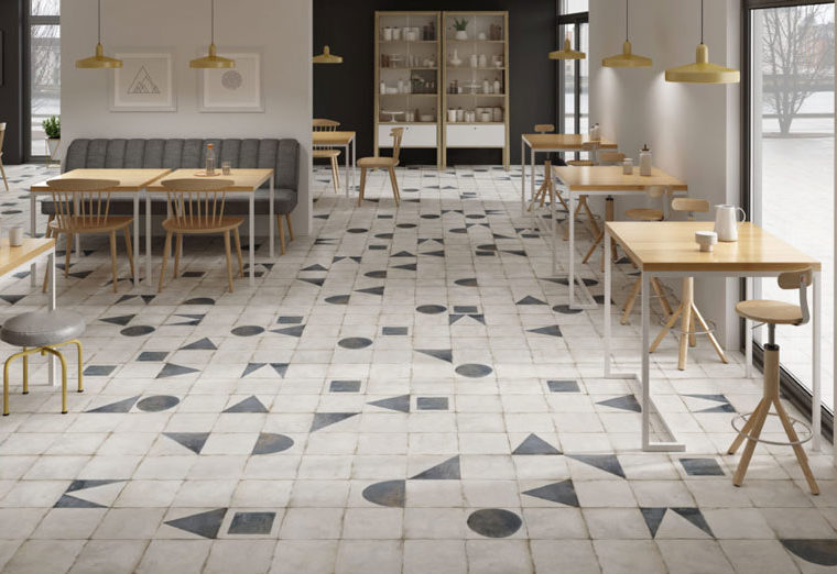 Worn, vintage style monochrome hallway floor tiles interspersed with pale black shapes.