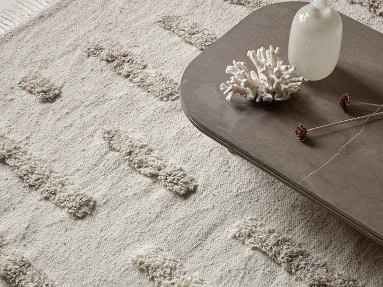 A tonal white tufted wool rug minimally styled, designed by Sera Helsinki.