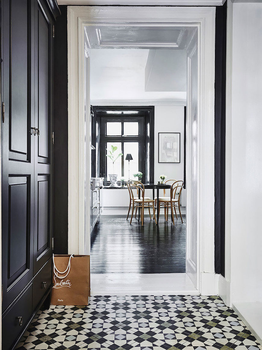 A very monochrome apartment featuring highly patterned monochrome hallway floor tiles with touches of blue and green.