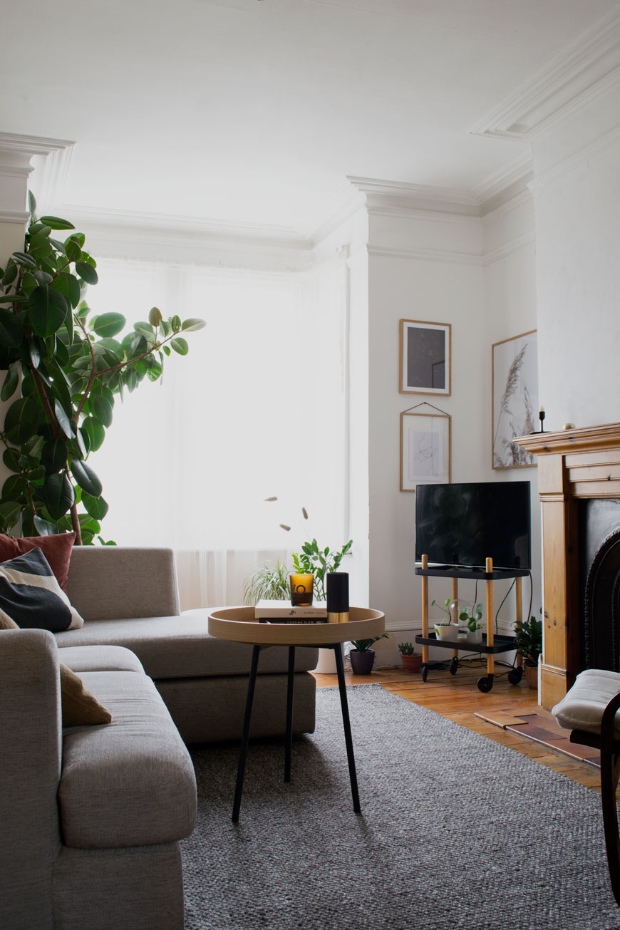 a white and grey Scandi-style living room with large grey timeless rug and round coffee table sitting on it.