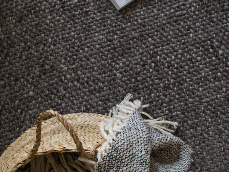 looking down onto grey wool flooring, with a basket on top of a timeless rug from British heritage brand Habitat.