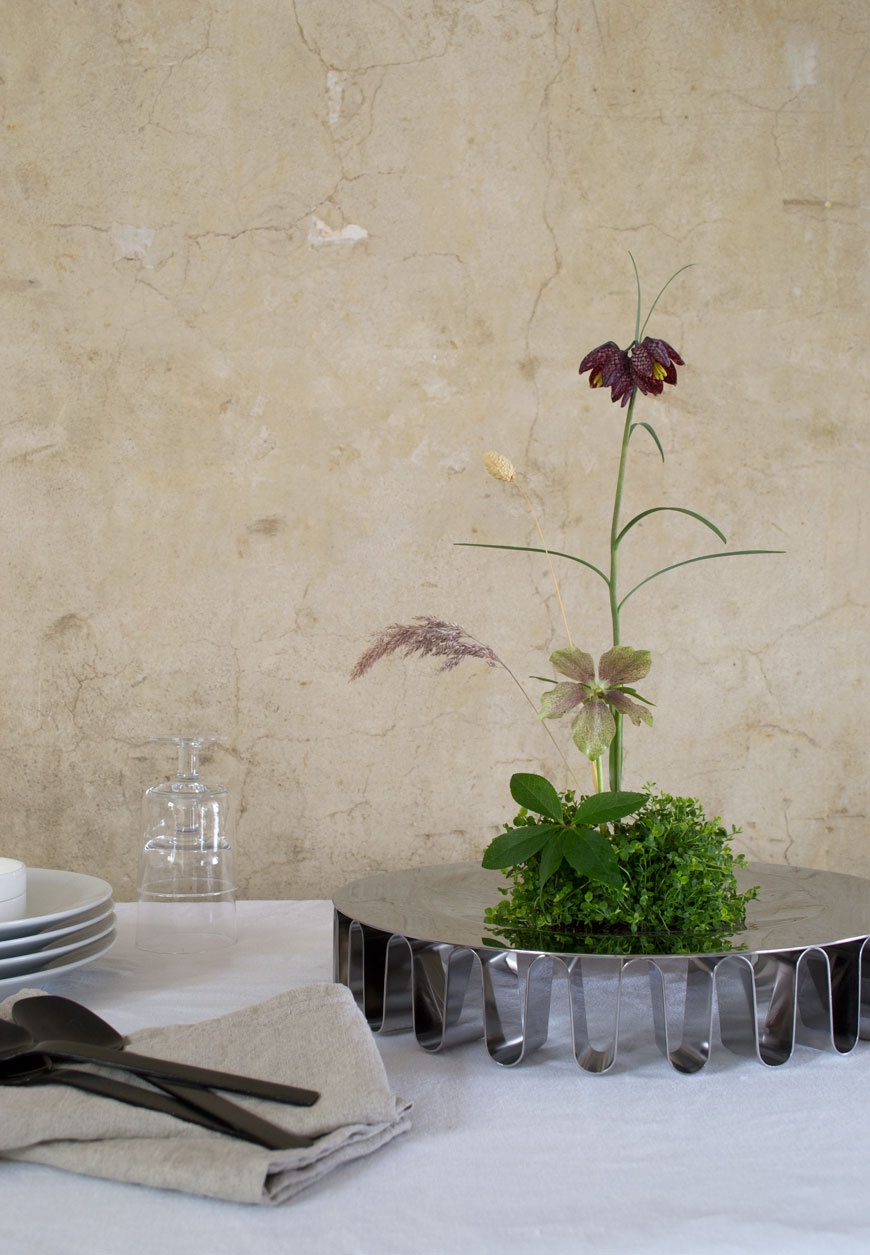 Japanese Ikebana arrangement on a Frequency collection centrepiece on a table.