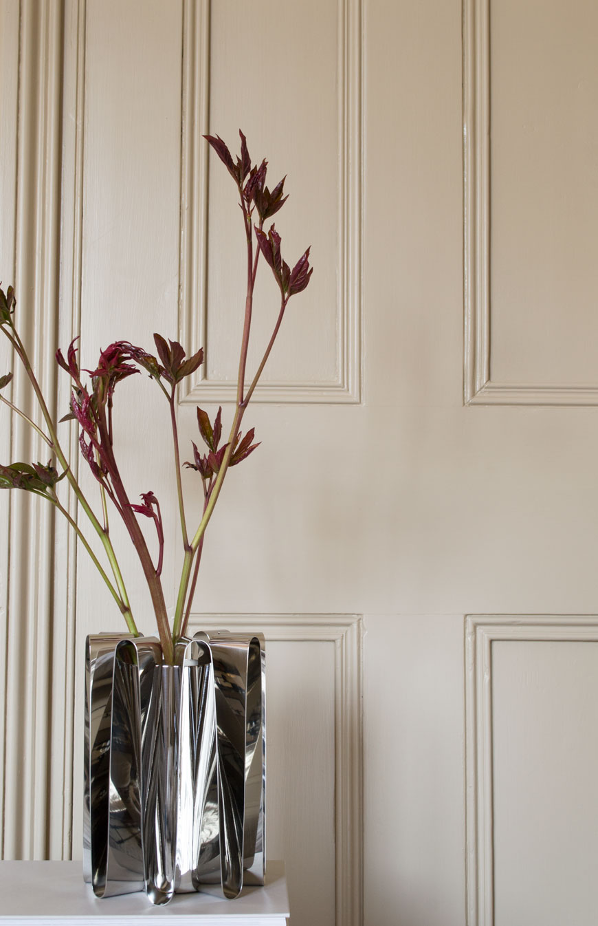 Frequency collection steel vase by Georg Jensen against a beige panelled door