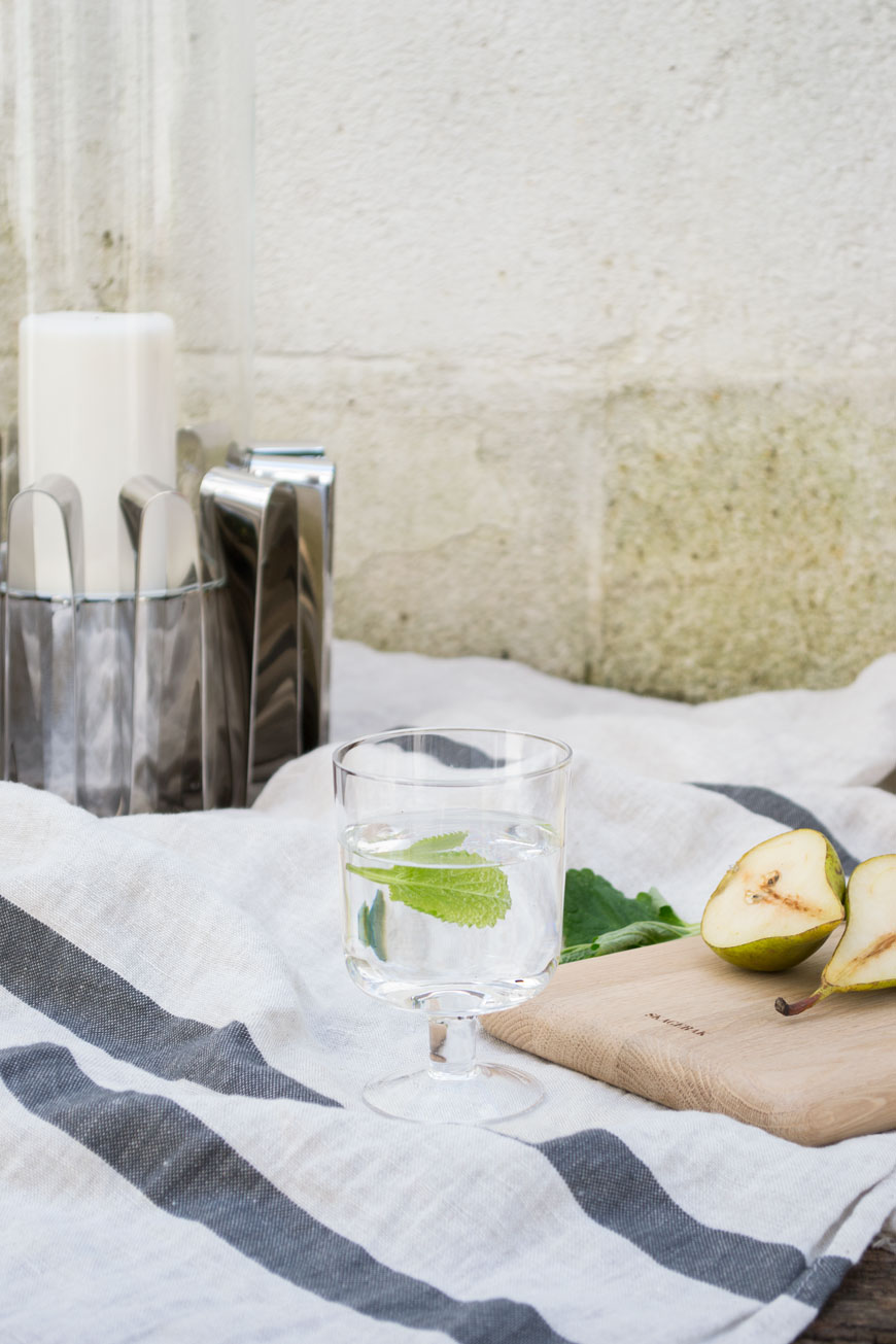 A glass of mint water and a Frequency collection hurricane lantern in a Scandi style garden.