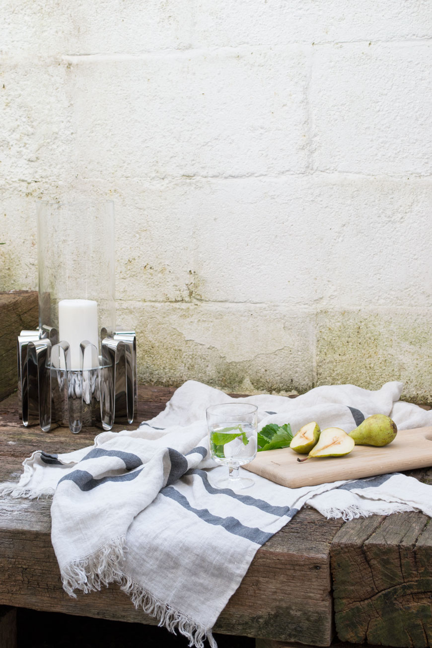 Still life with pears and a linen towel styled with the Frequency collection Hurricane lantern.