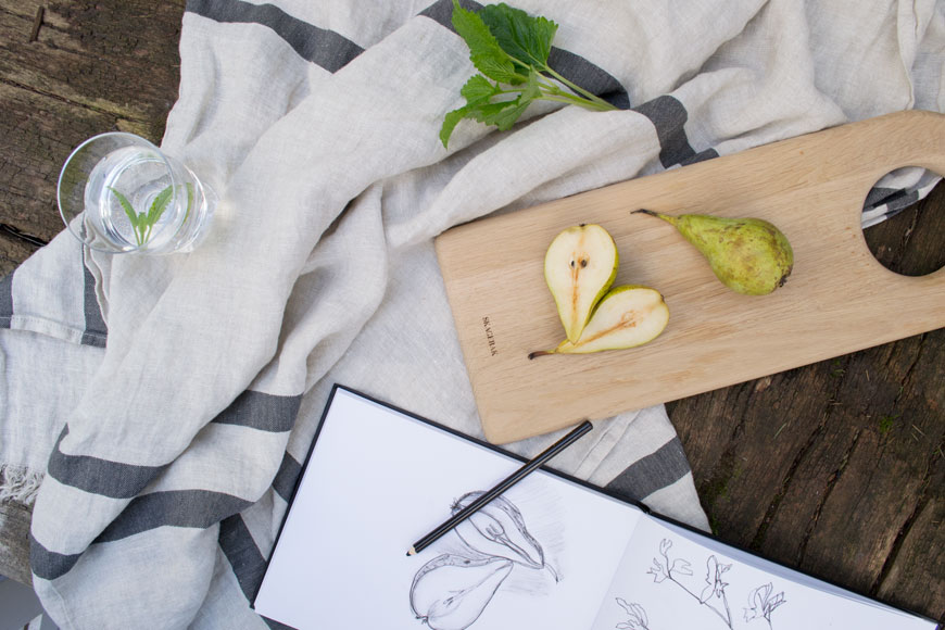 A fresh, summery still life with pears, a sketch book and a linen towel.