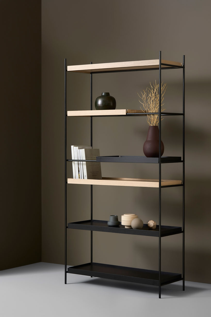Sleek and slender Tray Shelf in black and natural oak in a minimalist setting, designed by Woud.