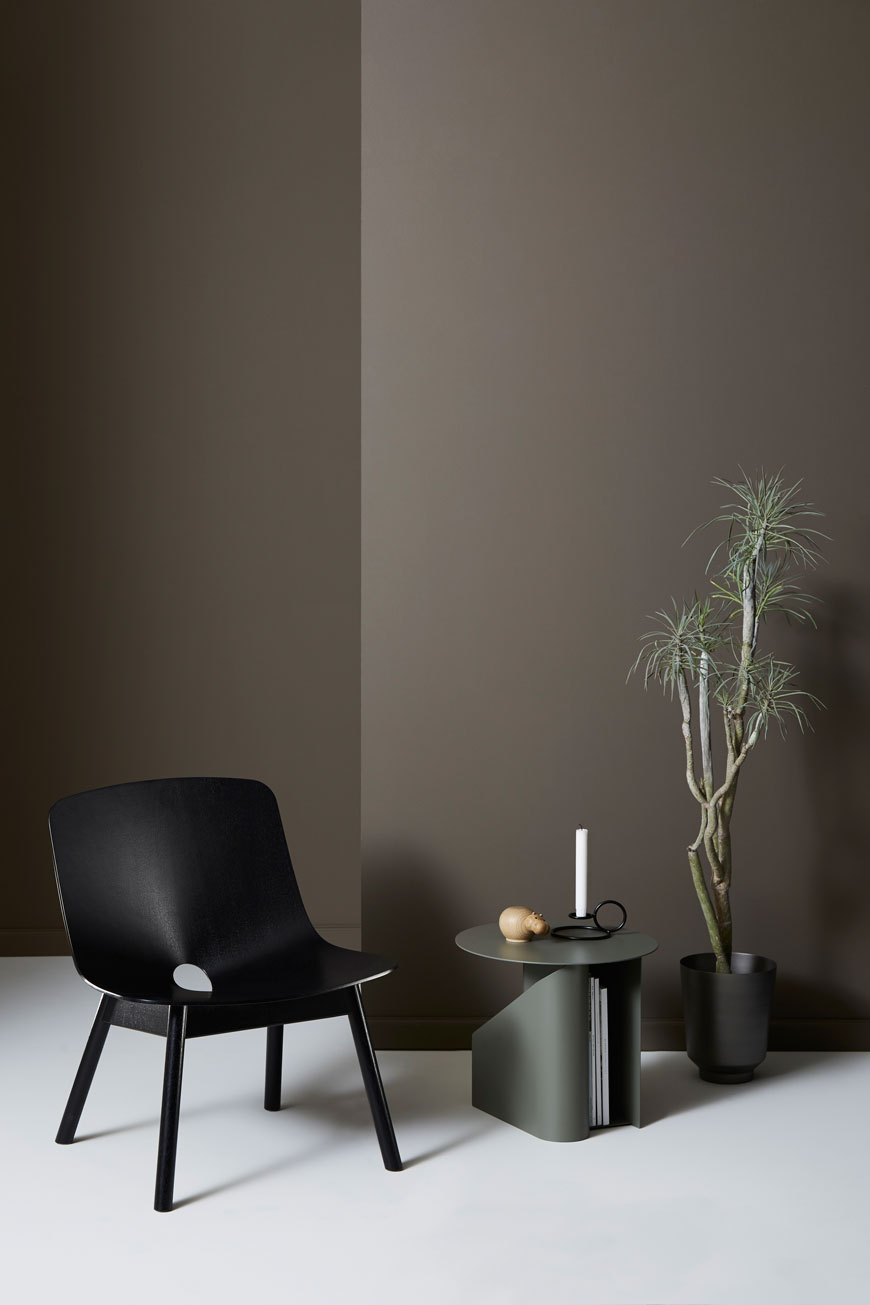 Dark and moody minimalist styling with a black ash lounge chair and dark brown walls, designed for Woud.