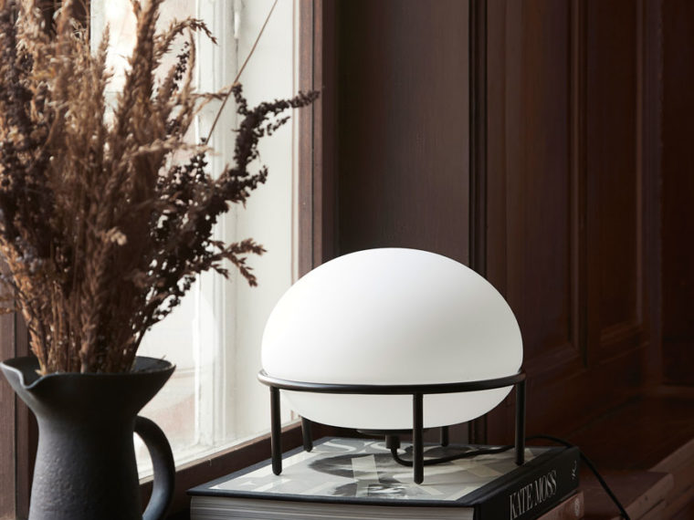 The Pump lamp with a black metal frame and opaline glass globe inspired by hot air balloons and designed for Woud.