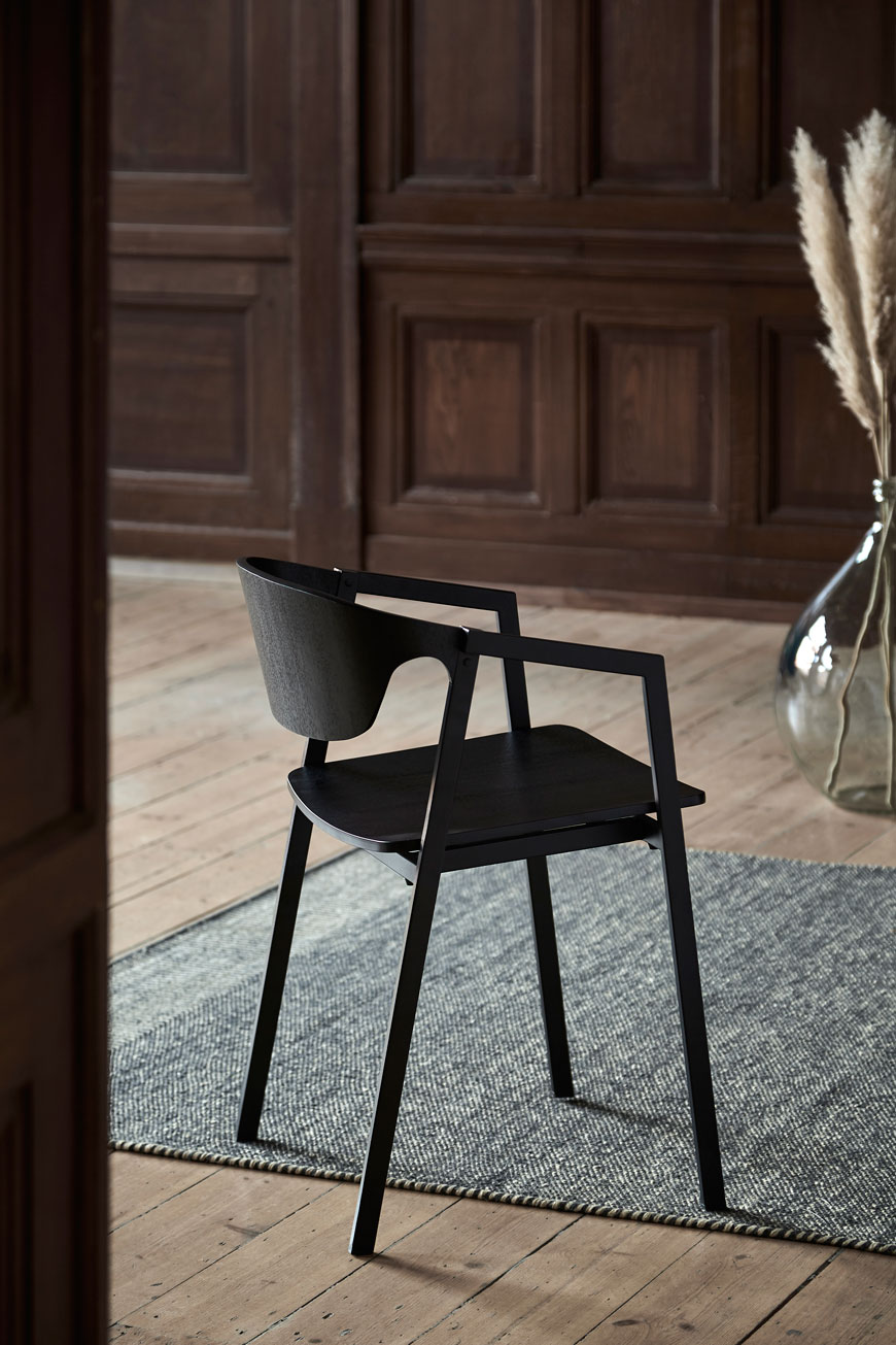 Woud design's latest Nordic dining chair in a minimalist setting with pampas grasses in a vase.