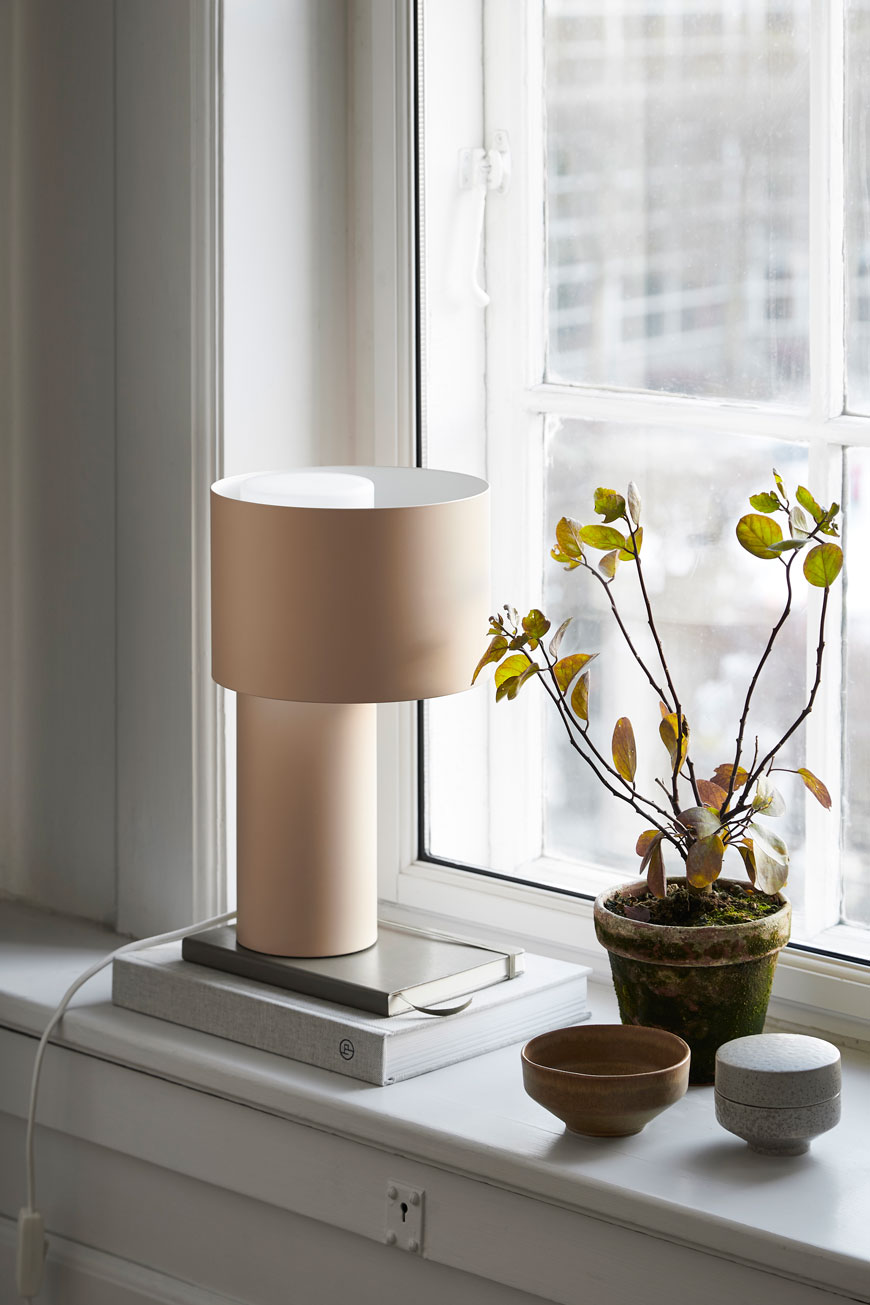 Soothing tones of the Tangent lamp styled on a windowsill with a stack of books, designed for Woud.