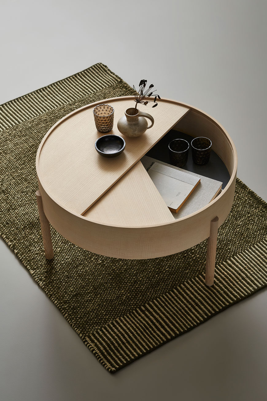The round ash wood Arc coffee table with a storage cubby inside, designed for Woud.