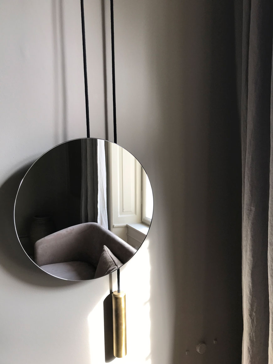 Round mirror with brass rope detail reflects back a grey chair in the New Works showroom.