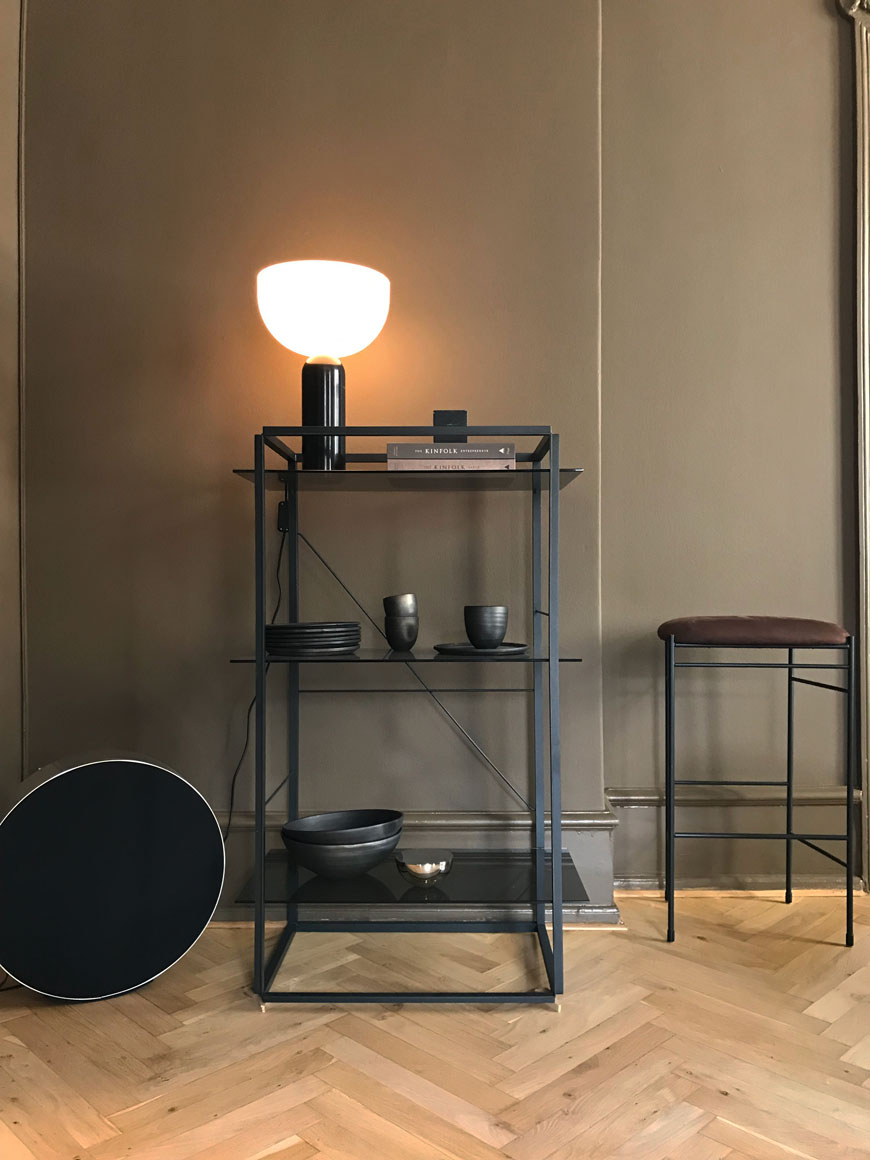 A round Bang and Olufsen speaker sits beside a black metal shelving unit at the New Works showroom.