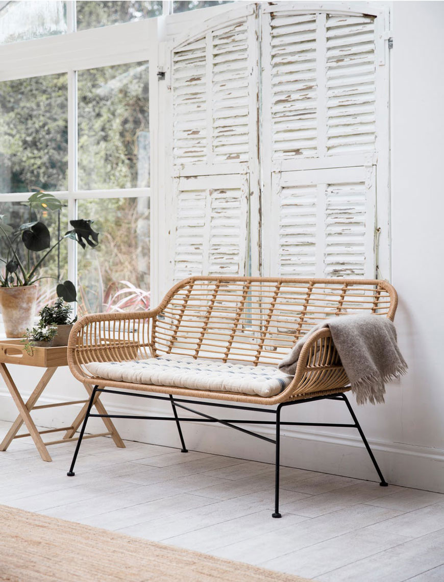 Stylish, sustainable outdoor furniture in woven bamboo with black steel legs, sitting in a garden room with white washed walls