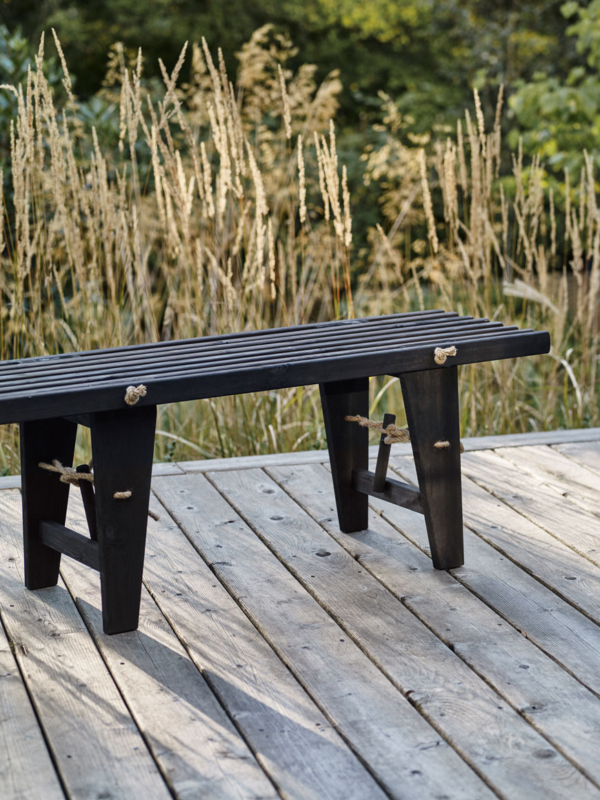 Oiled black slatted wooden bench, a striking example of contemporary outdoor furniture in a prairie garden.