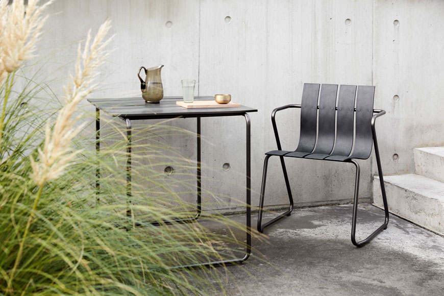 Award winning outdoor furniture designed by Mater, the Ocean chair sits against a concrete garden wall with pampas grasses.