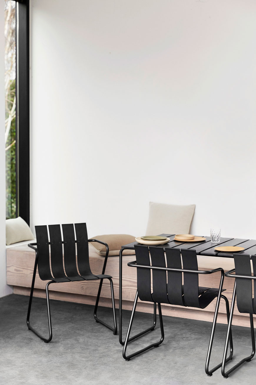 black recycled plastic outdoor furniture with slatted seats in a bright and open interior.