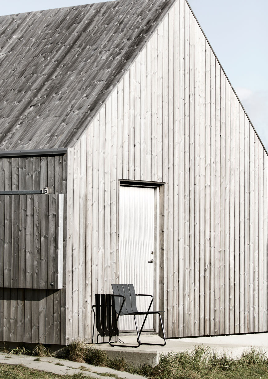 Black recycled plastic outdoor furniture sitting against a weathered grey cabin.