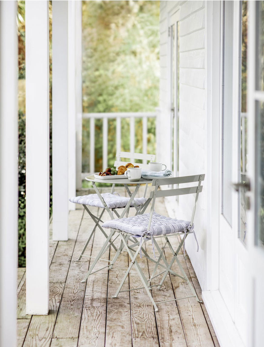 Classic bistro style outdoor furniture styled on a wooden veranda from Garden Trading,