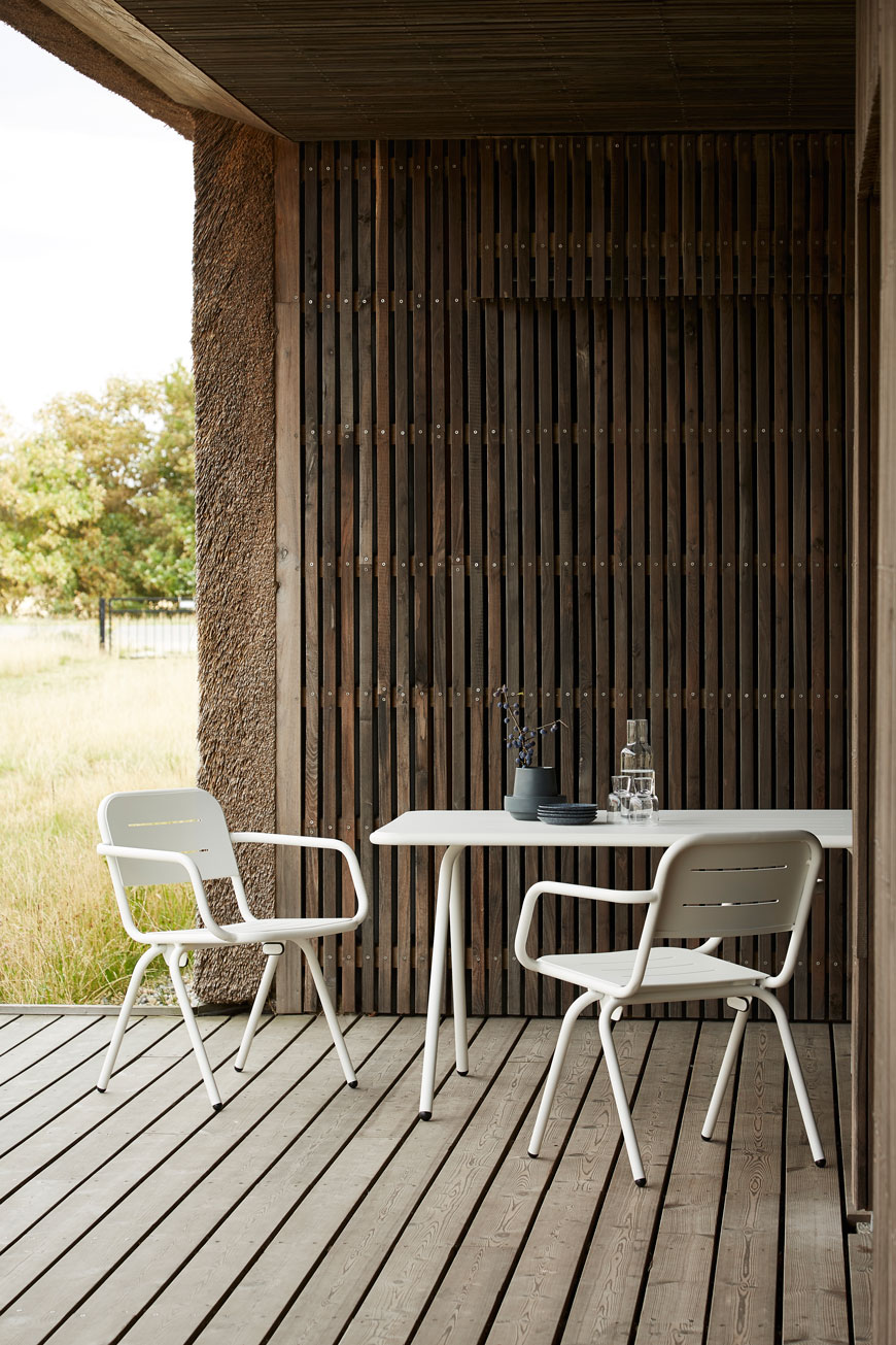 white metal bistro style outdoor furniture in a contemporary garden with decking.