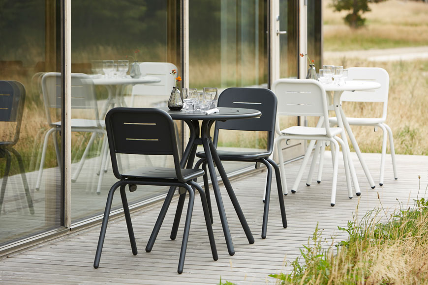 Monochrome outdoor furniture with curved metal frames, designed by Woud.