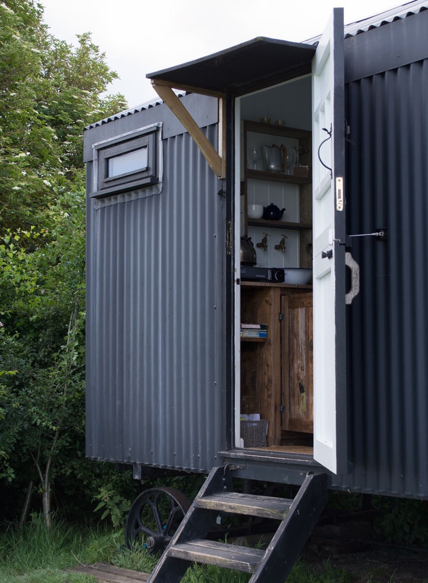 Modern rustic black shepherd's hut on a cozy stay at Elmley Nature Reserve.