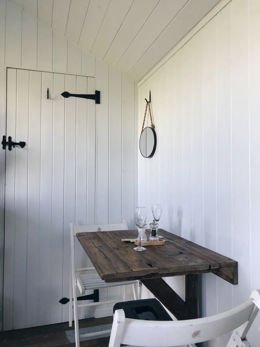A fold down wooden table and chairs save space inside the white wood clad Vanellus shepherd's hut.