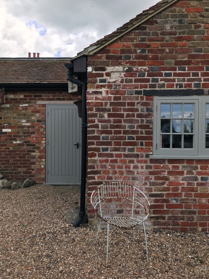 An old brick outhouse with grey green painted door and window at Elmley in Kent.