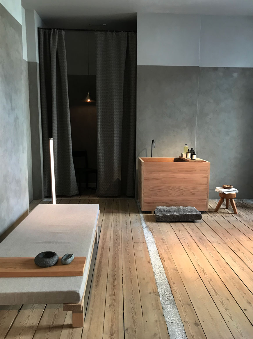 A Japanese wooden bath tub and a simple daybed in a minimalist room to relax at Frama Studio at 3daysofdesign