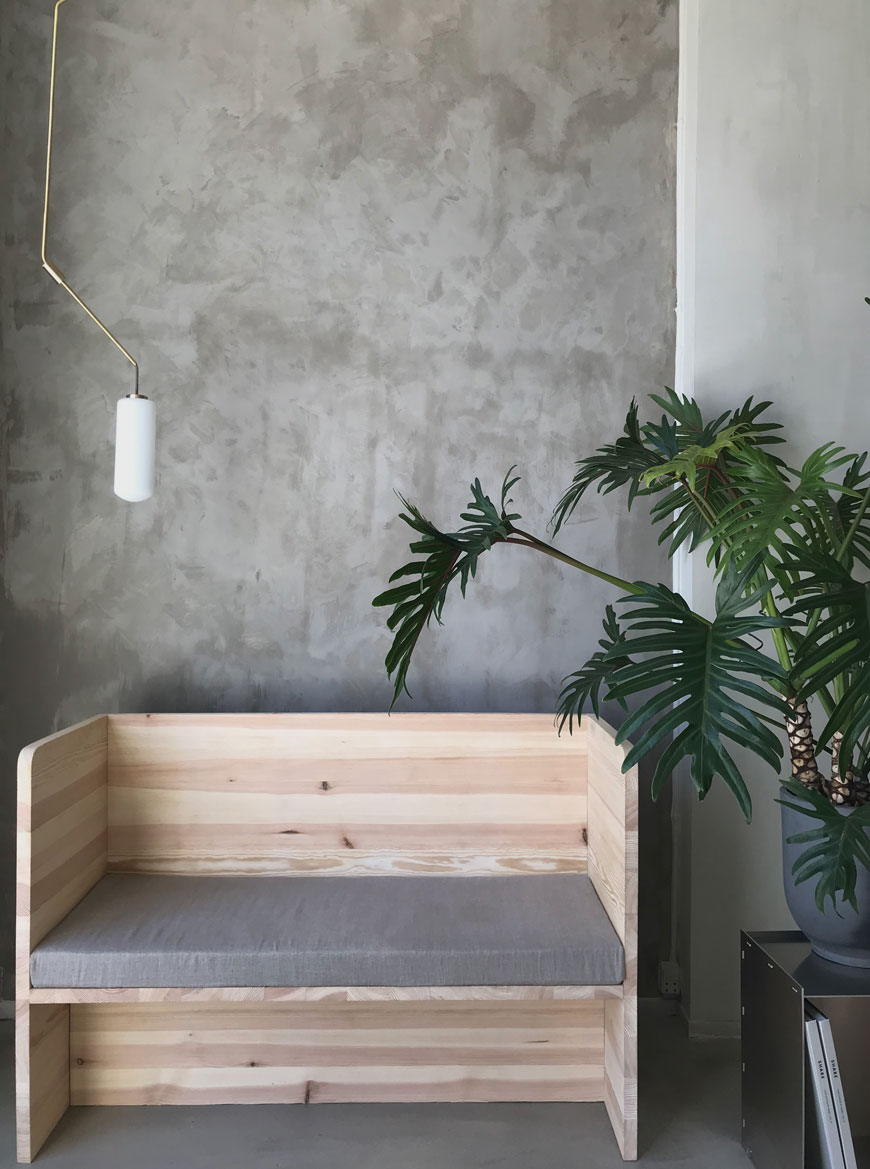 A wood bench in a minimal room at Frama Studio with a highly textured grey lime washed wall at 3daysofdesign.