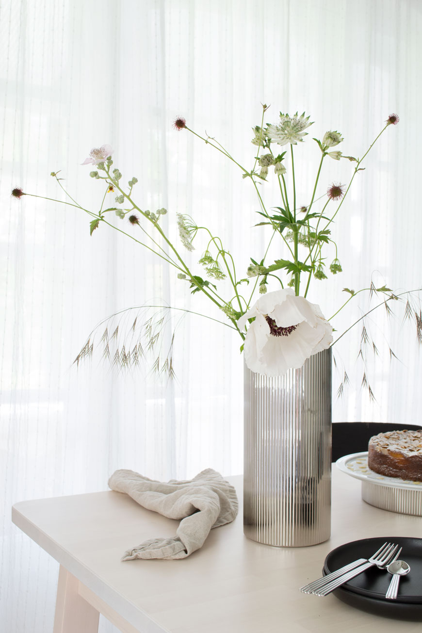 Loose white garden and wild flowers styled in a stainless steel ridged vase by Sigvard Bernadotte.