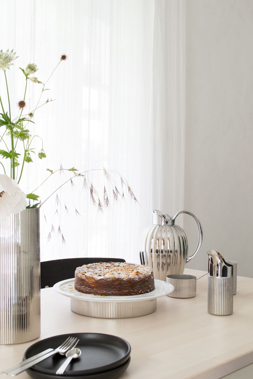 Looking across a table set for a midsummer afternoon tea with stainless steel tableware and wild flowers.