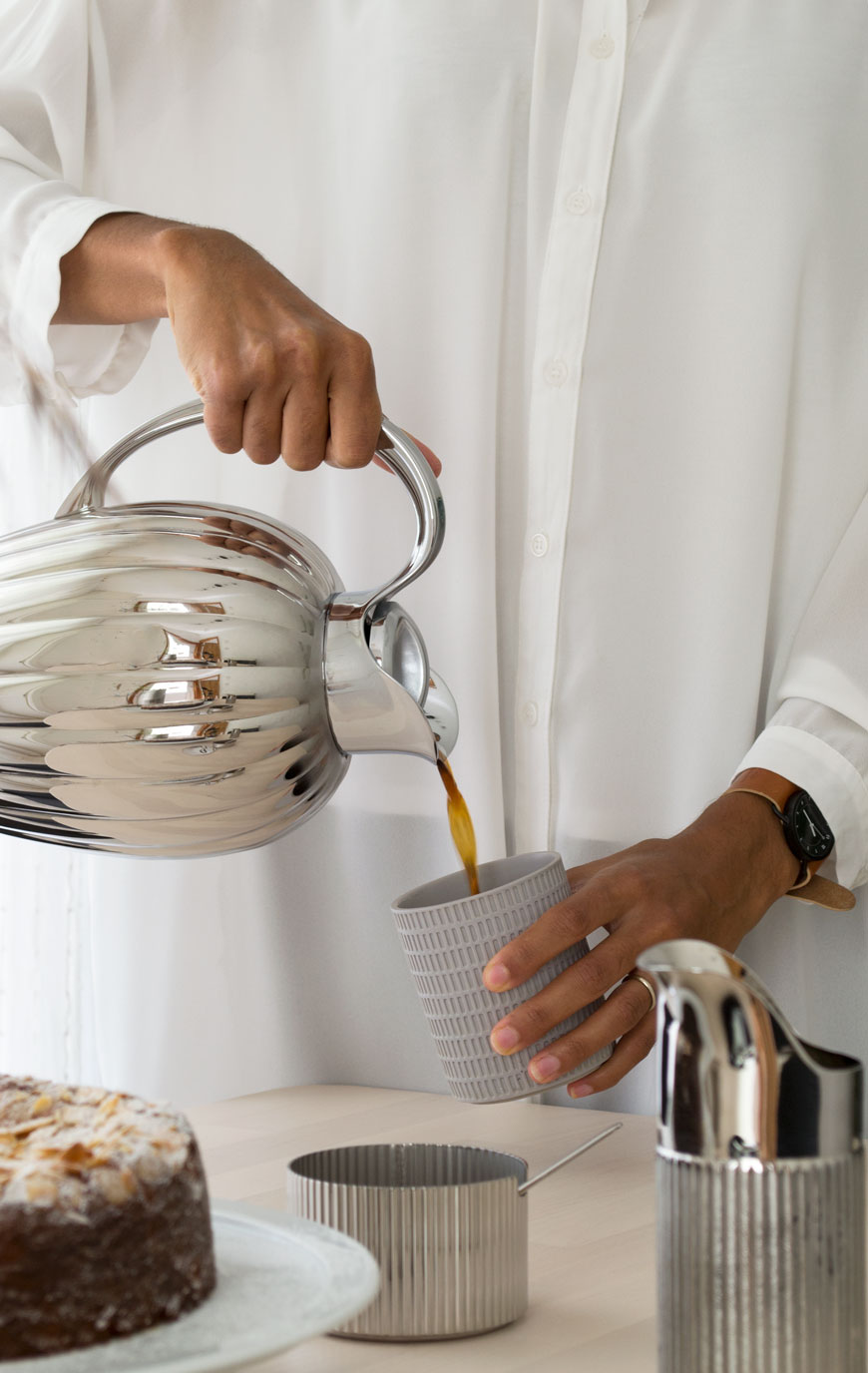 A woman pouring coffee from a stainless steel thermo into a grey ceramic beaker.