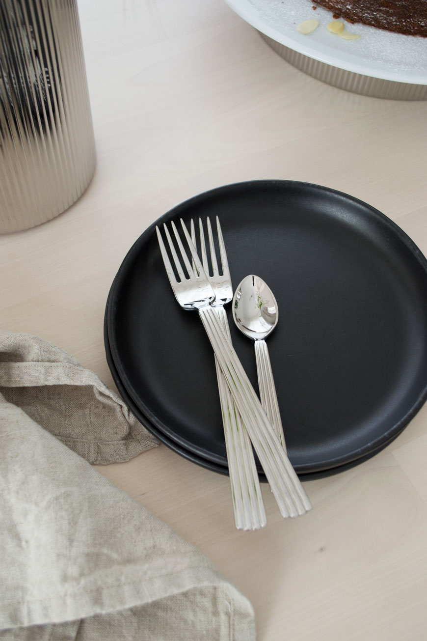 Modern, stylish cutlery from the Georg Jensen collection sitting on a stack of black side plates.