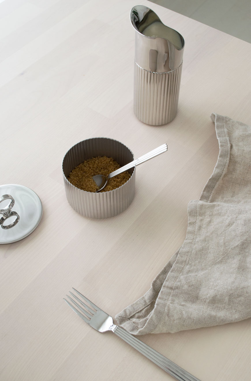 Minimalist styling of a ridged stainless steel milk jug and sugar pot with natural linen napkin.