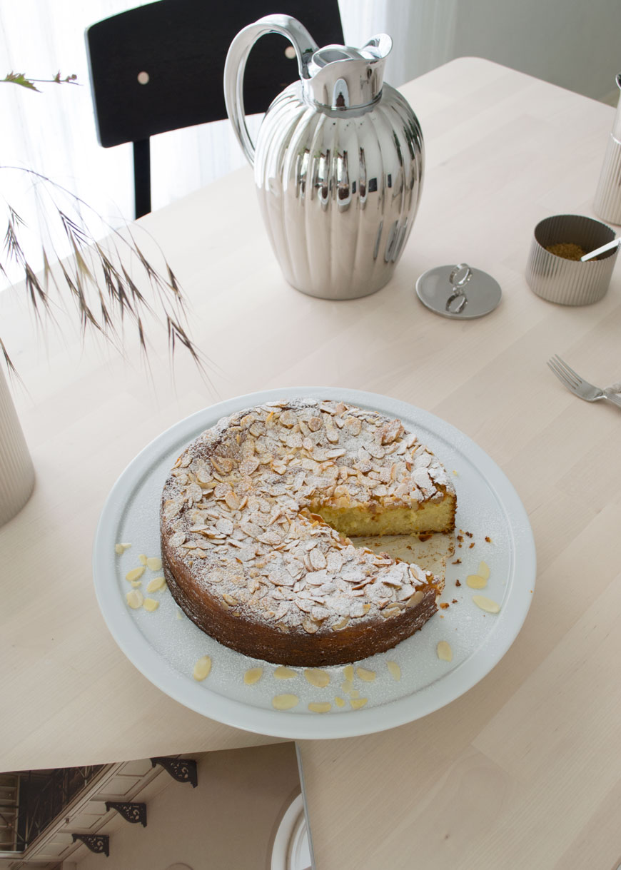 Looking down onto an orange and almond cake on a white serving plate with a thermo of coffee in the background