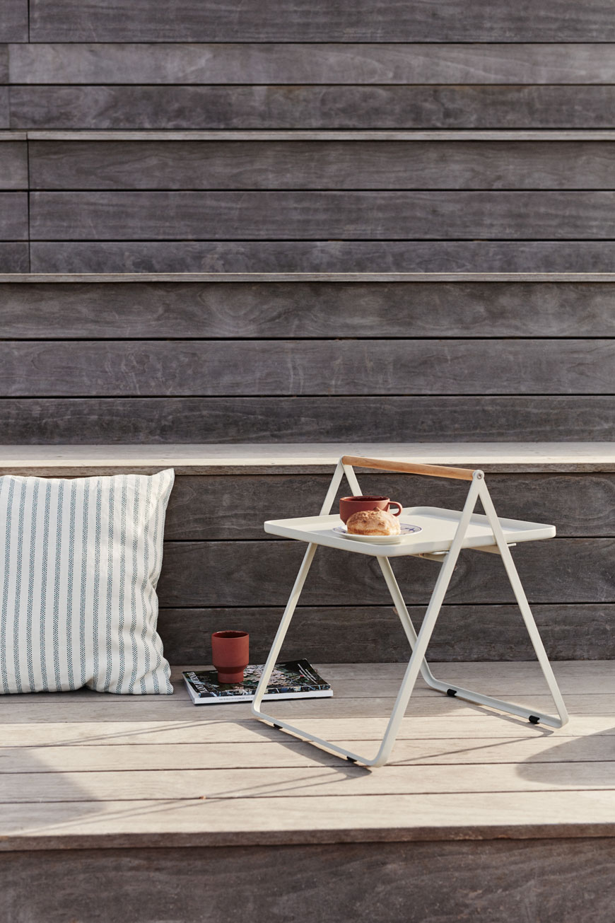 A white metal side table used as outdoor furniture on a wooden desk with striped cushion.